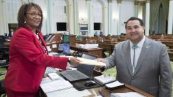 Assemblymember Ramos handing bill across the desk