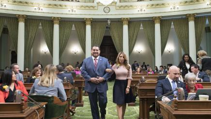 Assemblymember Ramos walking down the chamber floor with 2019 Woman of the Year Kristine Scott